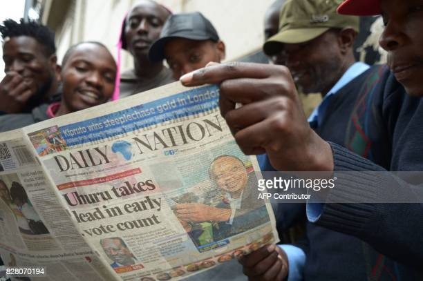 A group of men read a local newspaper on August 9 2017 in Kiambu north of Nairobi a day after the presidential election President Uhuru Kenyatta...