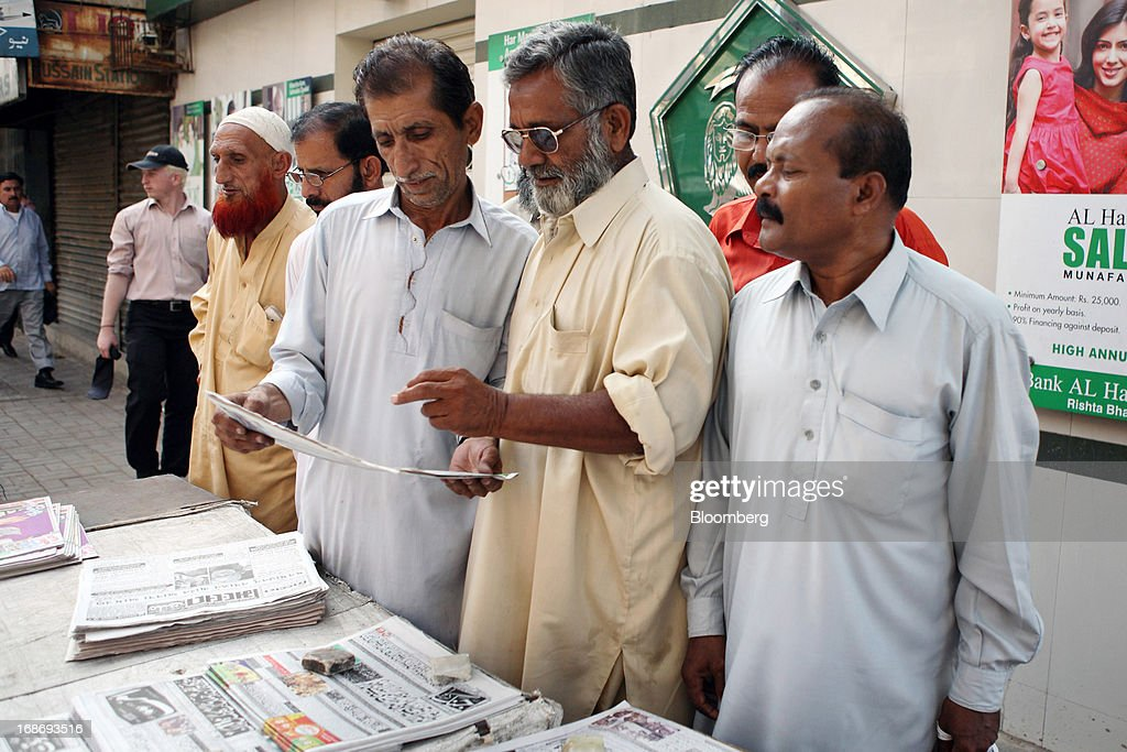 A group of men read a newspaper in Karachi, Pakistan, on Monday, May 13, 2013. Nawaz Sharif was headed for a record third term as prime minister of Pakistan as unofficial results from a landmark election gave him the convincing win he sought to tackle a slumping economy and growing militancy. Photographer: Asim Hafeez/Bloomberg via Getty Images