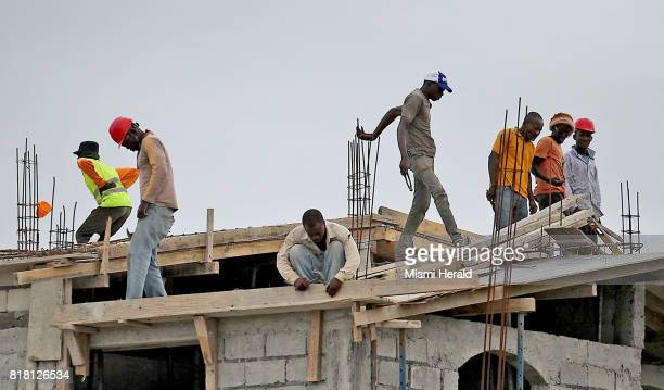 A group of men reconstruct a large house in late June near Port Salut nearly nine months after Hurricane Matthew struck the area