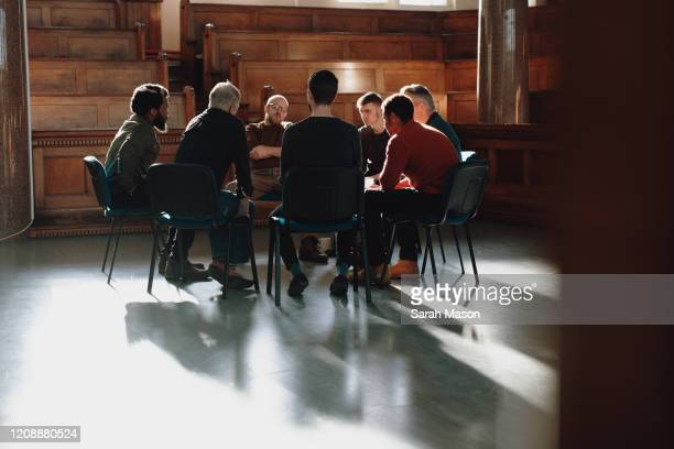 group of men, seated in therapy session - spirituality stock pictures, royalty-free photos & images