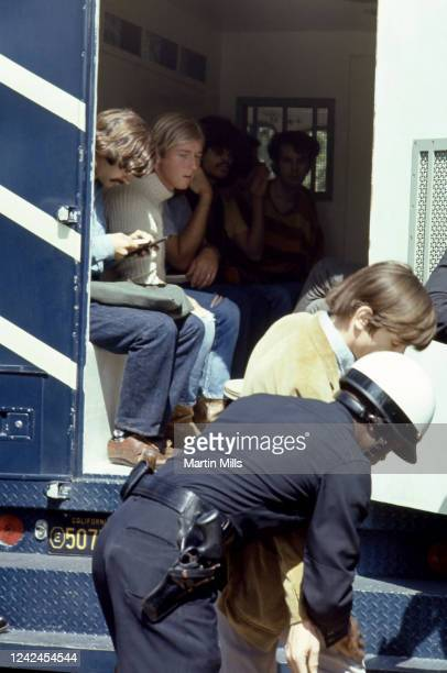 Group of men sit in the back of the police bus as they watch a man being arrested by Los Angeles Police officers during a student protest against...