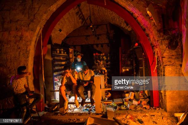 Group of men sit near the entrance of a shop damaged after a large explosion on August 4, 2020 in Beirut, Lebanon. There was a structure fire near...