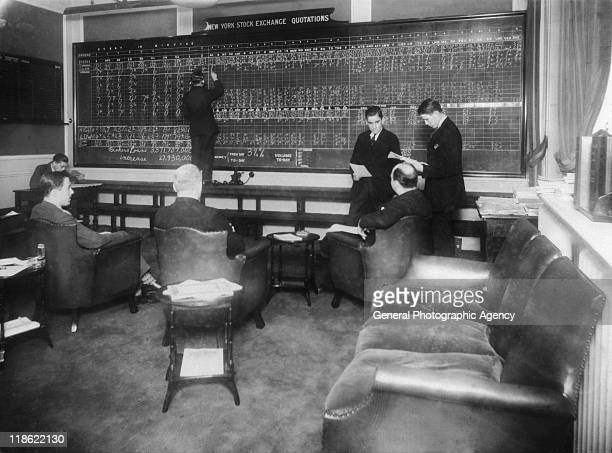 A group of men sitting and standing before a large chalkboard headed 'New York Stock Exchange Quotations' with a man updating the figures on the...