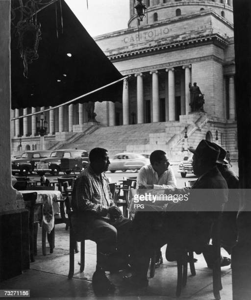 A group of men sitting at a pavement cafe in front of the domed government building El Capitolio 1950s