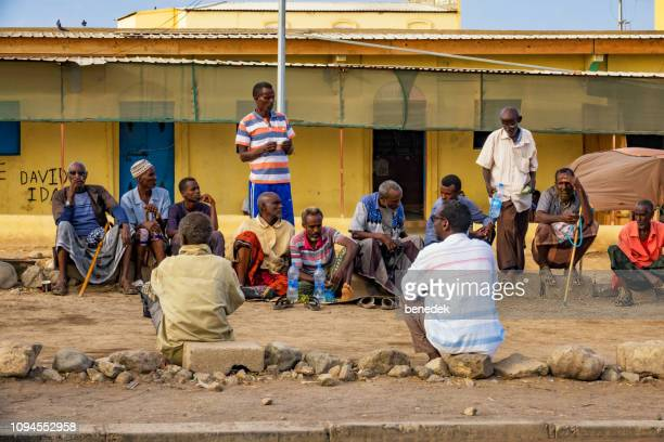 group of men socialize in the outskirts of djibouti city djibouti - djibouti stock pictures, royalty-free photos & images