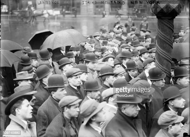 A group of men stand in the rain while gathered outdoors to listen to the latest news about the Lawrence Massachussetts textile strike New York...