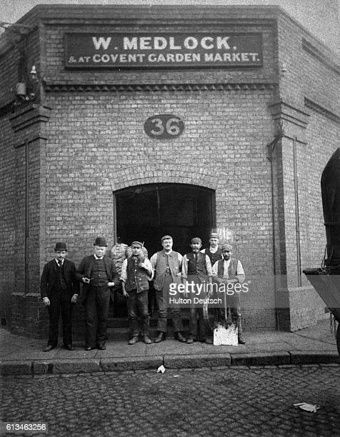 A group of men standing in front of the Covent Garden Market