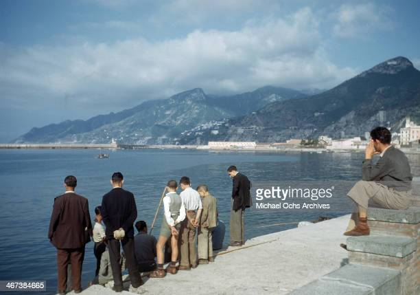 A group of men stop and talk to a fisherman on the Gulf of Salerno in SalernoItaly