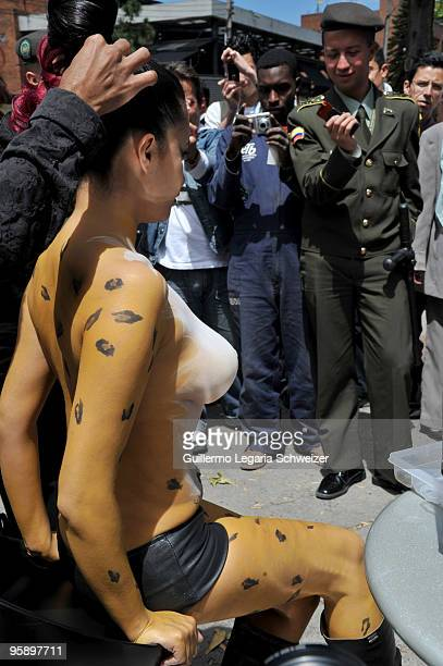 A group of men take pictures of a half naked model as she gets her hair fixed on the streets of Bogota on January 20 2010 in Bogota Colombia The body...