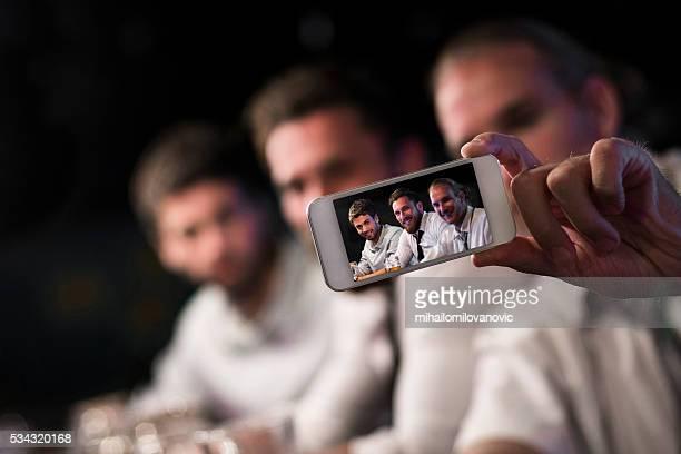 Eine Gruppe von Männer nimmt selfies