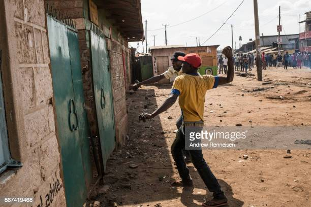 A group of men throw rocks at a man behind the gate of a compound they were trying to loot in the Kawangware slum on October 28 2017 in Nairobi Kenya...