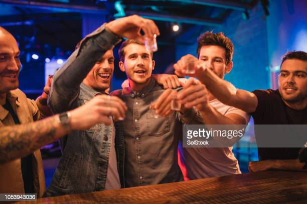 group of men toasting their drinks - hitting stock pictures, royalty-free photos & images