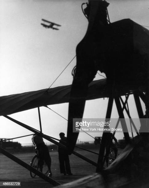 A group of men two of whom are on bicycles stands against the silhouette of a propeller biplane as another biplane flies in the sky New York 1930