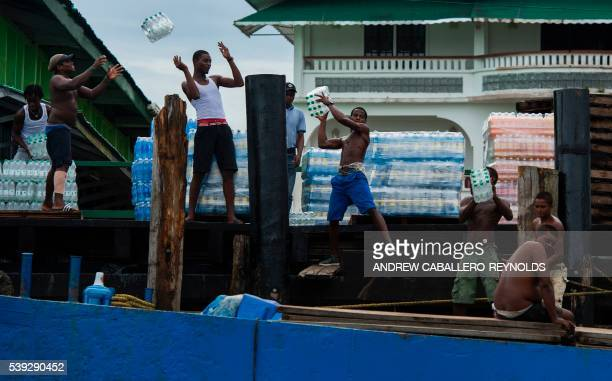 TOPSHOT A group of men unload water from a boat in the town of Bartica Guyana on June 6 2016 Bartica is a town at the confluence of two major rivers...