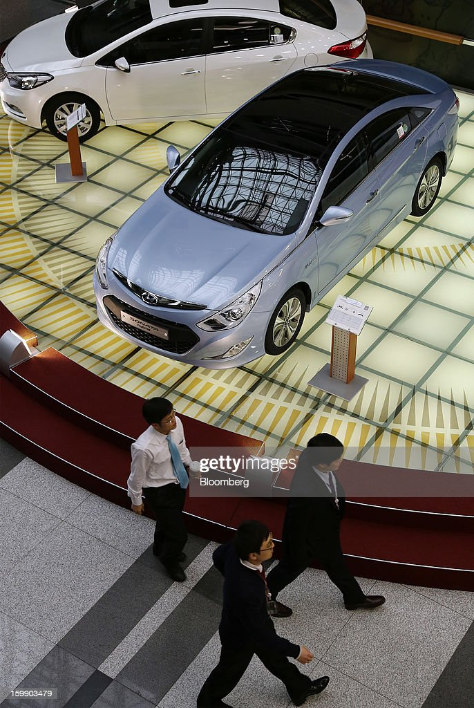 A group of men walk past a Hyundai Motor Co. Sonata hybrid vehicle in the showroom at the company's headquarters in Seoul, South Korea, on Tuesday, Jan. 22, 2013. Hyundai Motor Co. is scheduled to release fourth-quarter earnings on Jan. 24. Photographer: SeongJoon Cho/Bloomberg via Getty Images