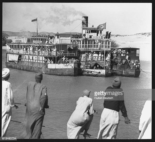 A group of men watch a steamboat moor up after its 40 hour journey from Aswan The steamboat which accommodates only first class passengers is flanked...