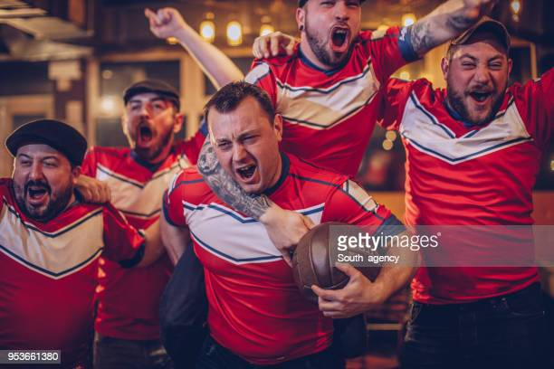 group of men watching game in pub - hooligan stock pictures, royalty-free photos & images