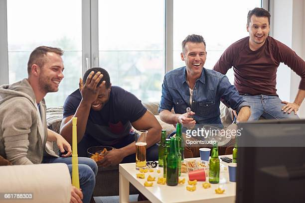 Group of men watching sports event on television with snacks and beers smiling