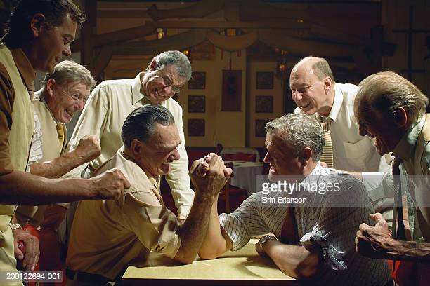Group of men watching two men arm wrestling