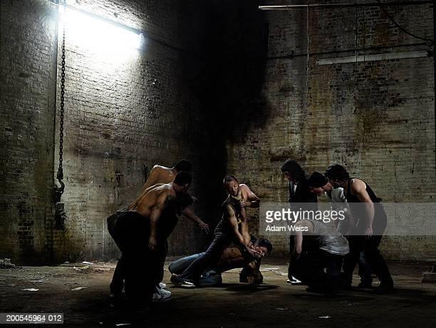 Group of men watching two men fighting in empty industrial space