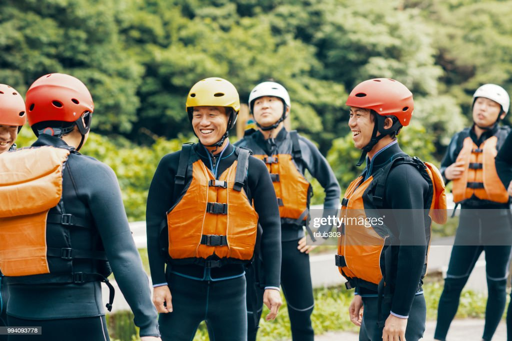 Group of men wearing life jackets and helmets before a river rafting tour : Stock Photo