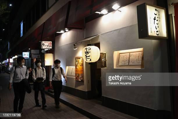 A group of men wearing protective masks walk past Izakaya bars in Yurakucho district on May 29 2020 in Tokyo Japan On May 25 Japanese government...