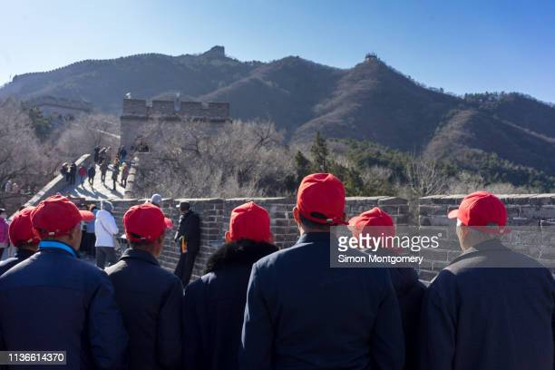 a group of men wearing red baseball caps on the great wall of china - men stockfoto's en -beelden
