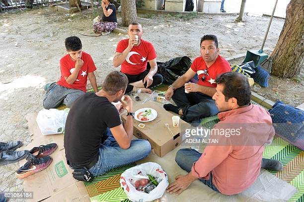 A group of men who were protesting against a failed military coup eat in a public garden next to Kizilay Square in Ankara on July 23 2016 Turkey's EU...