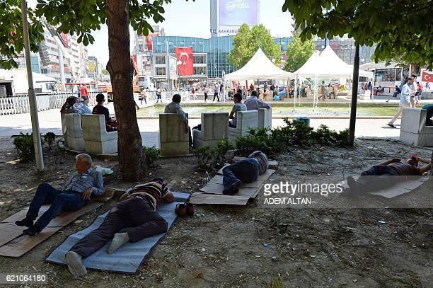 A group of men who were protesting against a failed military coup rest in a public garden in Ankara on July 23 2016 Turkey's EU minister said July 23...