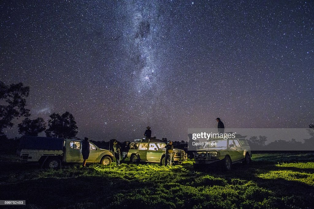 Group of men with four wheel drives look at stars : Stock Photo