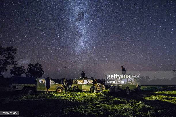 Group of men with four wheel drives look at stars