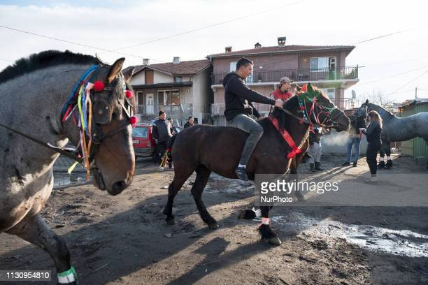A group of men with their horses gather in front of a neighbor's house in the Fakulteta neighborhood of Sofia March 16 2019 to receive blessings in...
