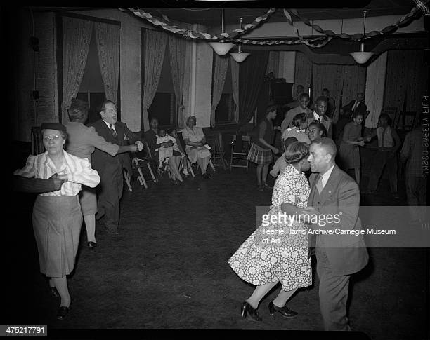 Group of men women one on right wearing floral dress boys and girls dancing in couples with band playing on stage in background in Hill City for barn...