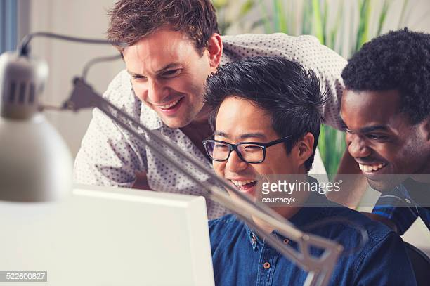 Group of men working on creative ideas with a computer