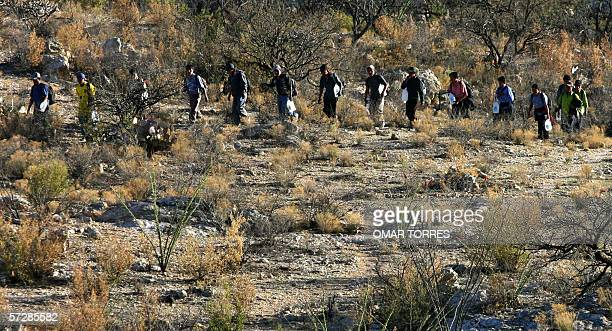 A group of Mexican immigrants walk through desert a hundred meters away from the MexicoUS border in Sasabe Sonora state Mexico carrying water cans...