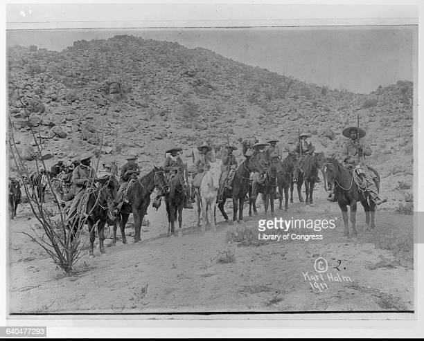 A group of Mexican rebels leave their desert camp on horseback during the Mexican Revolution