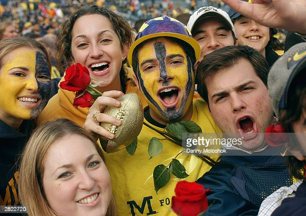A group of Michigan Wolverines fans celebrate their team getting invited to the Rose Bowl during as they won the 100th meeting against the Ohio State...
