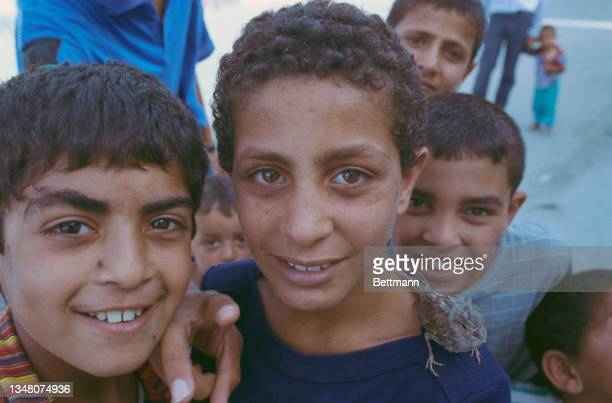 Group of Middle Eastern boys pose smiling in an unspecified area of the West Bank, 1988.