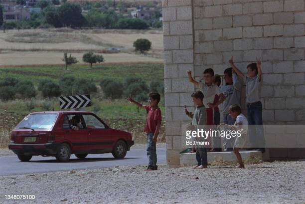 Group of Middle Eastern children waving at the passing traffic, as a red Chrysler Horizon drives along a road in an unspecified area of the West...