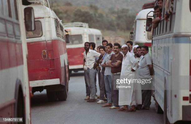 Group of Middle Eastern men gathered between buses and coaches in Jerusalem, Israel, 1988.