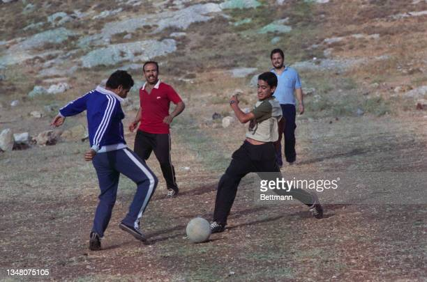 Group of Middle Eastern men playing football on a patch of land in Jerusalem, Israel, 1988.