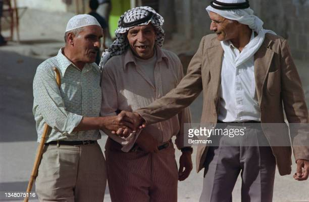 Group of Middle Eastern men, two wearing a keffiyeh with the third wearing a kufi, shake hands in an unspecified area of the West Bank, 1988.