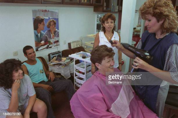 Group of Middle Eastern people sitting in a hairdressers as a woman sits smiling in a chair as a hairdresser stands holding a hairdryer, in an...