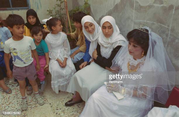 Group of Middle Eastern women and children, the women wearing hijabs alongside a woman wearing a white dress with a veil, possibly a wedding dress,...