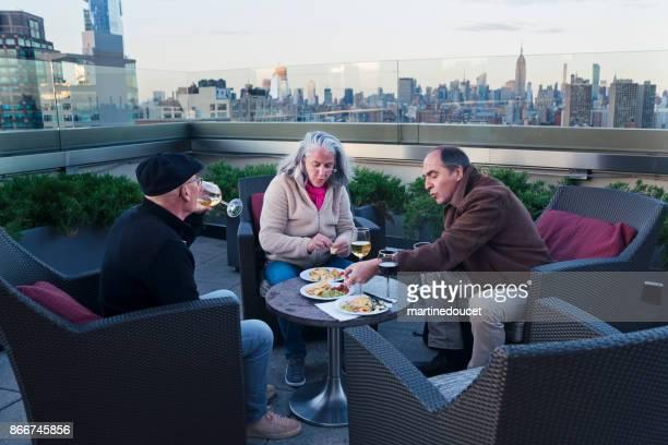 Grupp medelålders vänner under happy hour i New York
