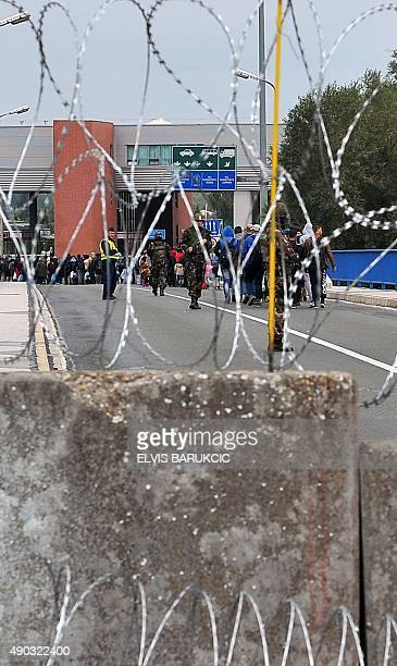 A group of MiddleEastern migrants walk towards a Hungarian border control checkpoint as they cross the HungarianCroatian border in the Croatian...