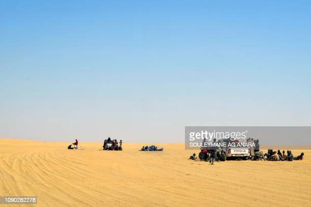 A group of migrant men mainly from Niger and Nigeria have a rest next to pick up vehicles on January 22 2019 during a journey across the Air dessert...