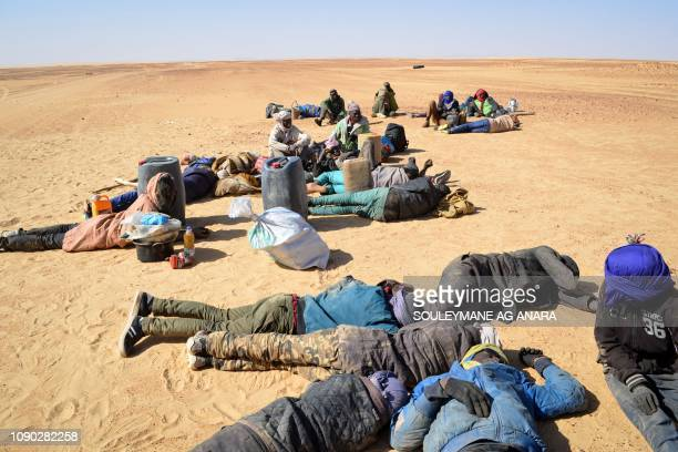 A group of migrant men mainly from Niger and Nigeria have a rest on January 22 2019 before carrying on with their journey across the Air dessert...