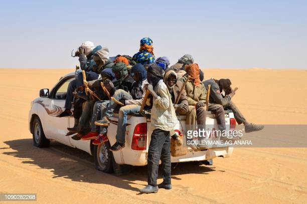 A group of migrant men mainly from Niger and Nigeria sit in the back of a pick up on January 22 2019 during a journey across the Air dessert northern...