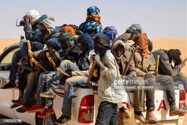TOPSHOT A group of migrant men mainly from Niger and Nigeria sit in the back of a pick up on January 22 during a journey across the Air desert in...